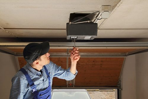 Garage door contractor working on repairing a garage door opener